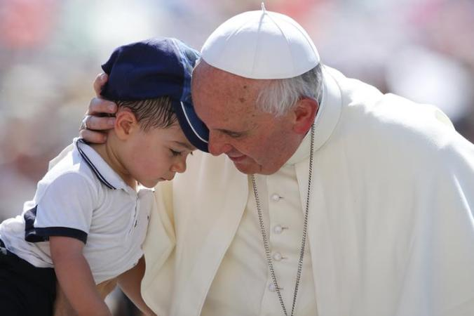 Pope Francis hugs a child as he arrives to lead the weekly audience in Saint Peter's Square at the Vatican June 19, 2013.   REUTERS/Stefano Rellandini     (VATICAN - Tags: RELIGION)